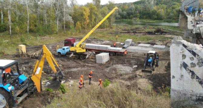 У  разлома моста в Станице Луганской начата укладка фундамента временного моста